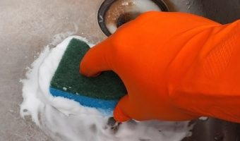 Scrubbing sink with scotch pad wearing rubber gloves.