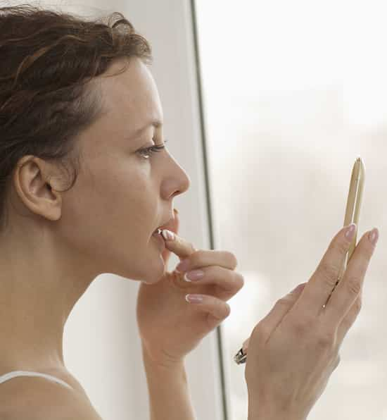 Profile shot of woman applying lipgloss by window at home