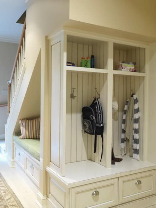 Small space hack! Transform the space under your stairs. Stair case with open cabinets on the ground floor for reading nook and coat/bookbag storage.