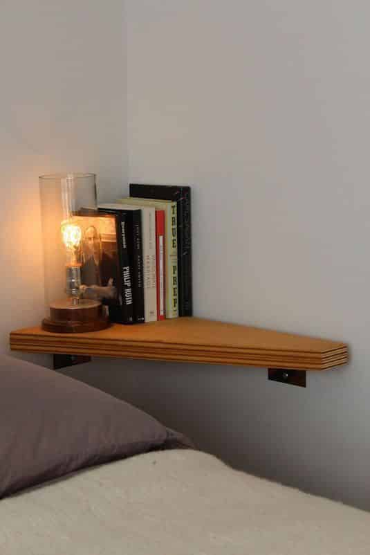 A corner shelf where there is no room for a nightstand as solution to a small bedroom storage ideas