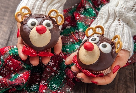 2 cupcake reindeer cupcakes with pretzel antlers and red M&M nose.