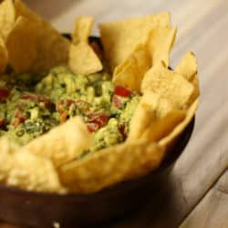 Bowl of avocado dip with chips ready for a party appetizer table
