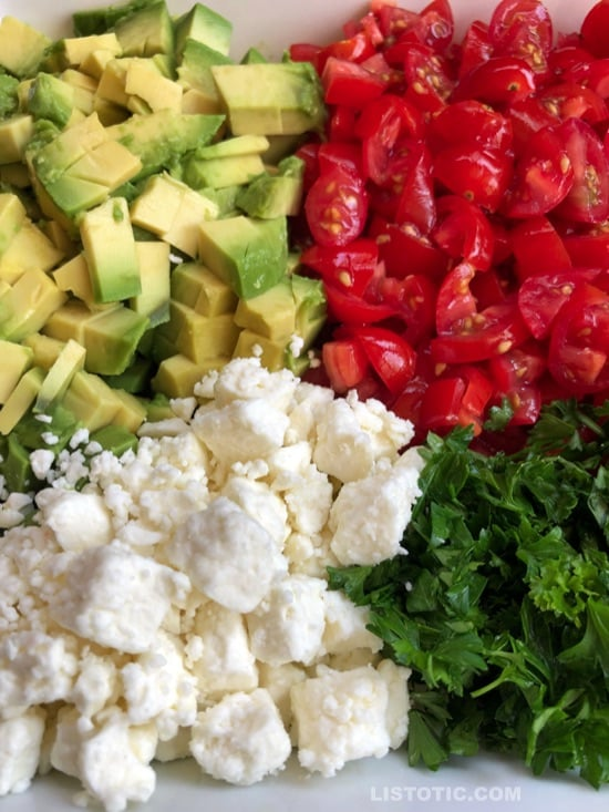 Avocado dip recipe with chopped avocado, diced cherry tomatoes, crumbled feta cheese, minced parsley