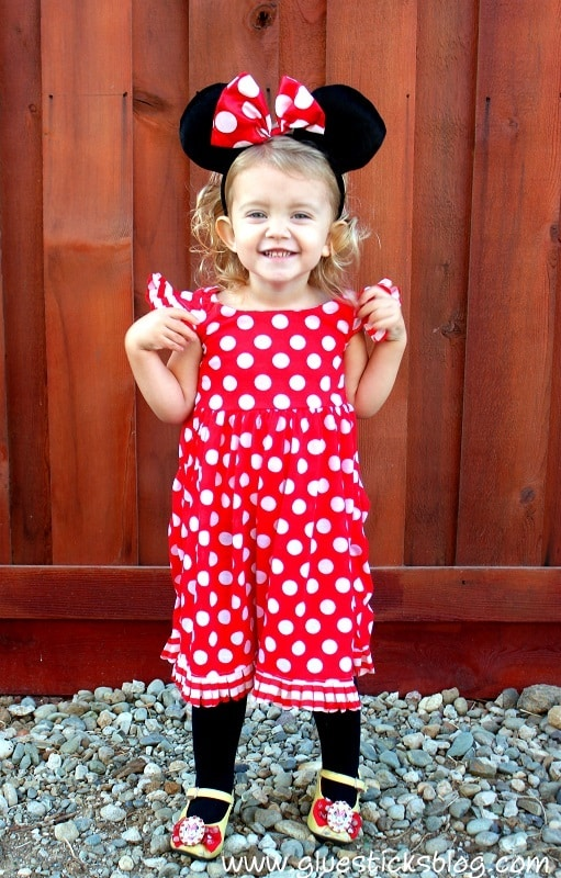 Toddler in Minnie Mouse costume with red polka dot dress and black mouse ears and bow.