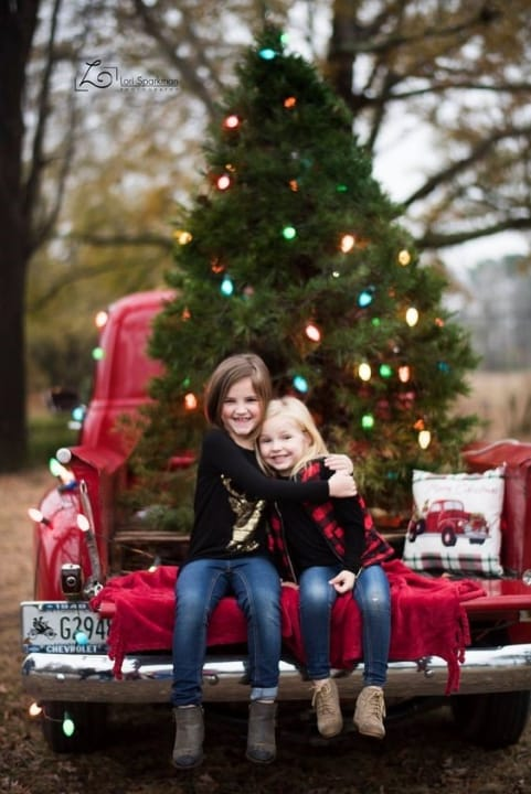 Adorable girls in front of Christmas tree for a greeting card.