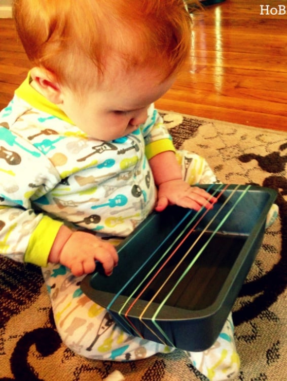 Easy DIY guitar using rubber bands and loaf pan for infants to create music.
