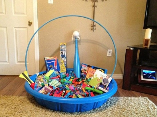 Kiddie pool filled with Easter themed gifts and summer toys such as a hula hoop, baseball bat and ball, bubbles, inflatable pool toys and more!