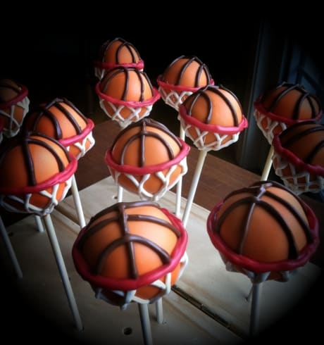Creative DIY cake pops made to look like basketballs inside a basketball hoop perfect for a March Madness Party Favor.