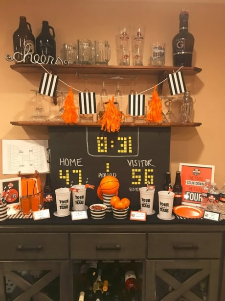 DIY scoreboard backdrop on a table decorated with Basketball themed centerpieces and March Madness party food.