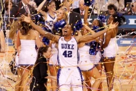 Duke basketball player with arms out and confetti falling as champions of historical March Madness Tournament final four Championship winner.