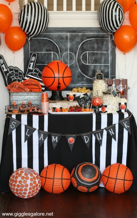 Basketball Theme decorations fill a table with basketball balloons at a March Madness Party for adults.