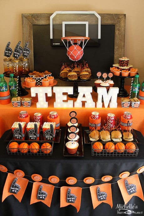 Party table decorations with Team centerpiece and basketball hoop for March Madness Basketball theme.