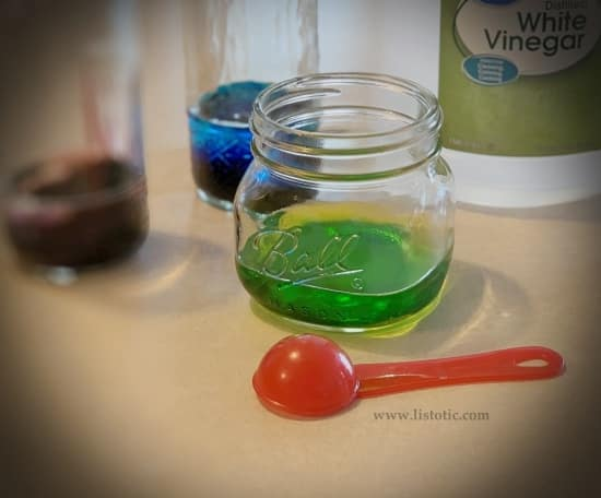 Mason jars with different colored food coloring and white vinegar prepped for Easter egg dying.