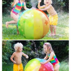 Kids playing around a bright colored large beach ball sprinkler outside in the summer time running and having fun with water spraying around them.