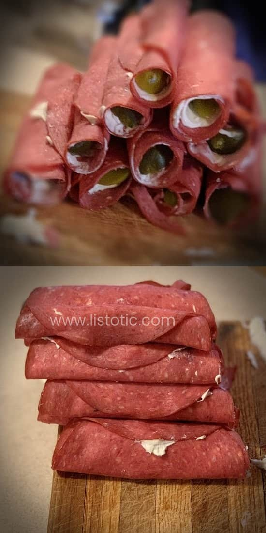 Stacks of rolled up dill pickle spears inside dried beef luncheon meat and cream cheese prepared for party appetizer.