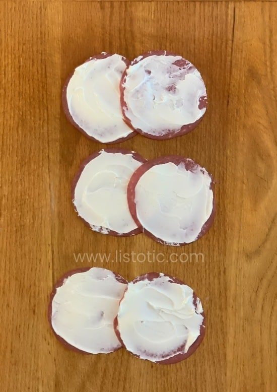 Slices of buddings dried beef smeared with cream cheese over-lapped on a wooden cutting board.