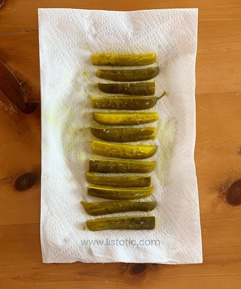 Roll of crisp dill pickle spears lined up on a white paper towel - ready to make dill pickle roll up recipe.