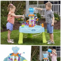 kids having fun in the summer time using a water table full of fun features. Child pouring water in to a water table with multiple ways for kids to play outdoors.