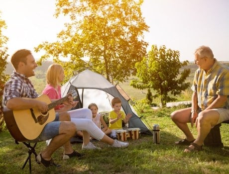 Family enjoying music and nature with their backyard camping adventure.