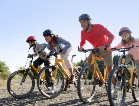 A family riding mountain bikes. They are all lined up ready to race. Great outdoor family fun!