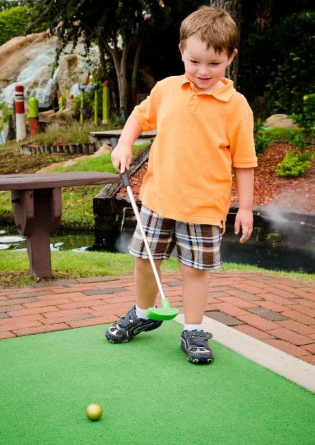 Young boy playing miniature golf.