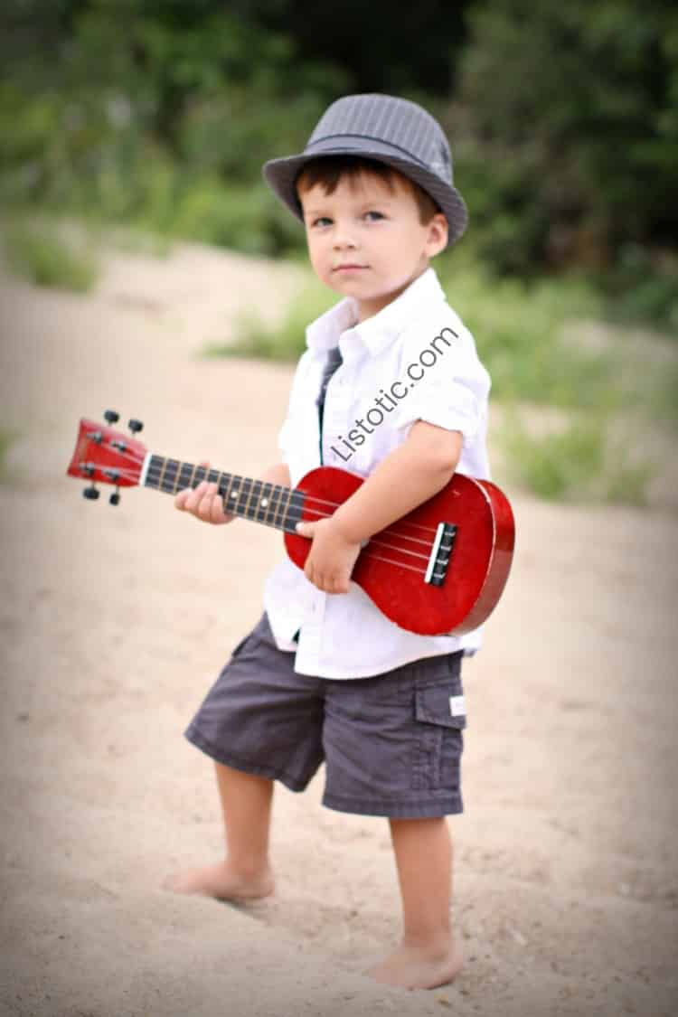 boy wearing a hat standing on a beach and holding a small red guitar