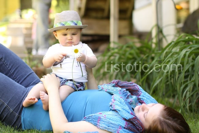 woman laying on back on the grass wearing a blue scarf and a baby sitting her stomach wearing a straw hat and holding a daisy.