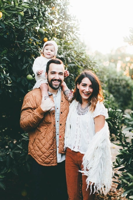Happy family of 3 in neutral colors and layered jackets and vests. Baby on the shoulders of dad standing together and smiling in front of an orange tree.