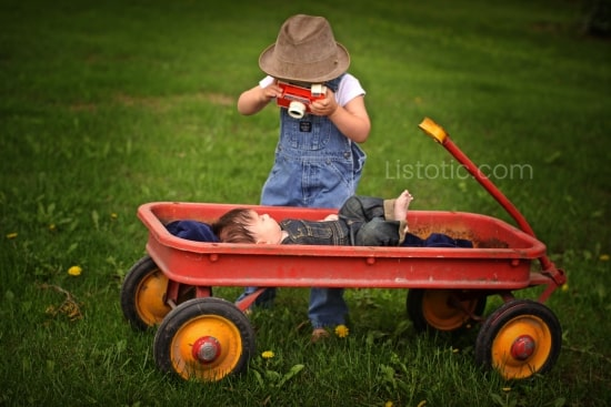 toddler in bib overalls and hat holding a Fischer price play camera leaning over a baby laying on his back in red wagon also wearing bib overalls. Boy standing is pretending to take a photo of the baby in the wagon.