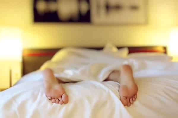 Exhausted woman laying in bed with just feet showing under a bed cover.