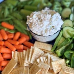 Crunchy fresh Cucumbers, pepper, carrots, celery, broccoli and sugar snap peas on a tray with crackers with a creamy cucumber dill veggie dip in the center.