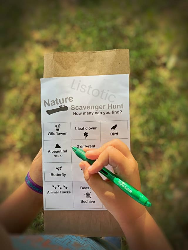 brown paper sack with free scavenger hunt printable attached. Child using a green pen to mark of the collected scavenger hunt items in a backyard or park.
