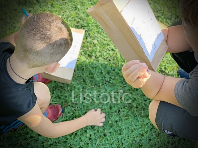two kids looking for clues on their nature scavenger hunt brown paper sacks with a bingo type design for a nature scavenger hunt outside in the park or backyard.