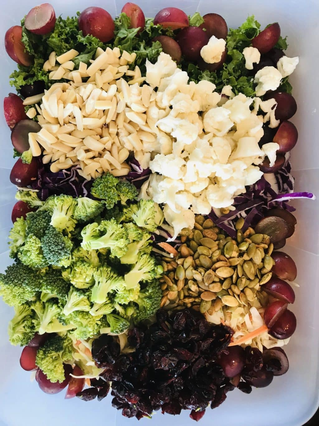 Whole 30 Detox Salad with broccoli, califlower, almonds, grapes, pumpkin seeds and more super foods.