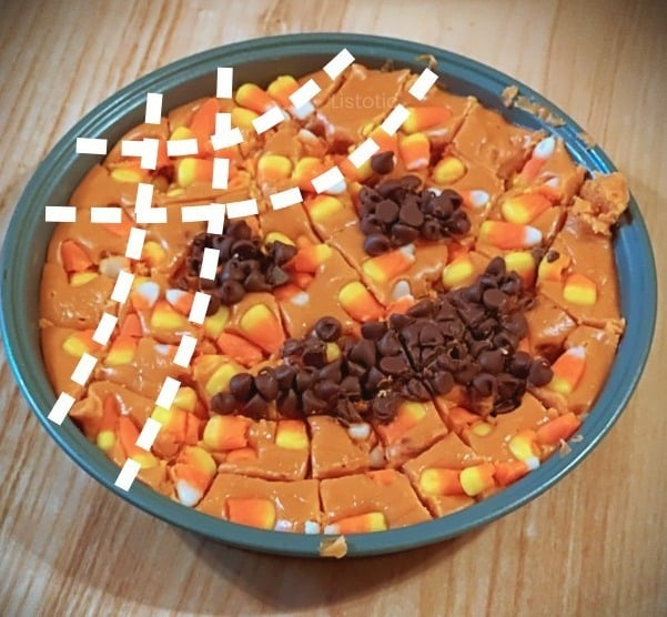 Pan of Halloween candy corn fudge that has been cut into bite size pieces for a Halloween party.