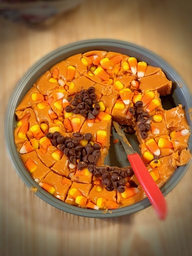 Cake pan of candy corn butterfinger fudge cut with knife still in it and pieces missing from the center of the dessert.