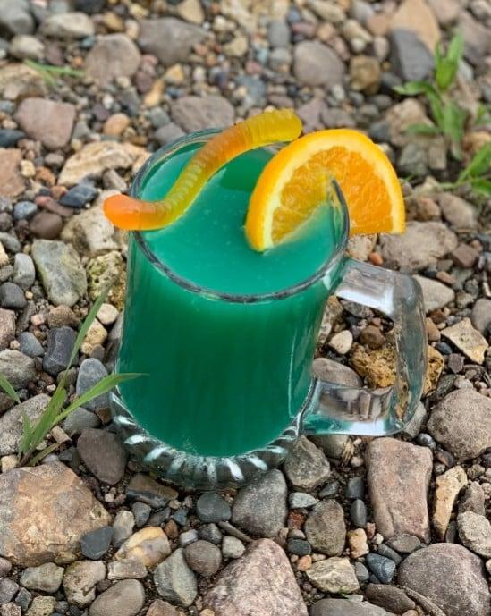 Blue hue beer cocktail with gummy worm and orange slice.