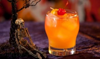 Orange cocktail with skeleton decorations for Halloween.