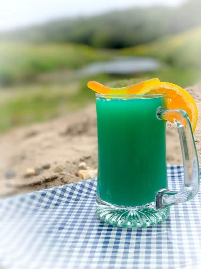 A greenish blue colored cocktail in a beer mug on a sandy creek side beach. Glass mug garnished with a gummy worm and orange slice on a blue gingham patterned tray.