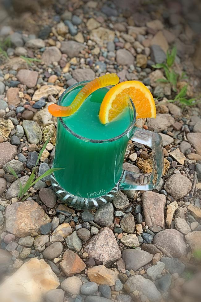 Beer mug full of blueish green river water cocktail recipe on a rocky river bank garnished with orange slice and gummy worm.