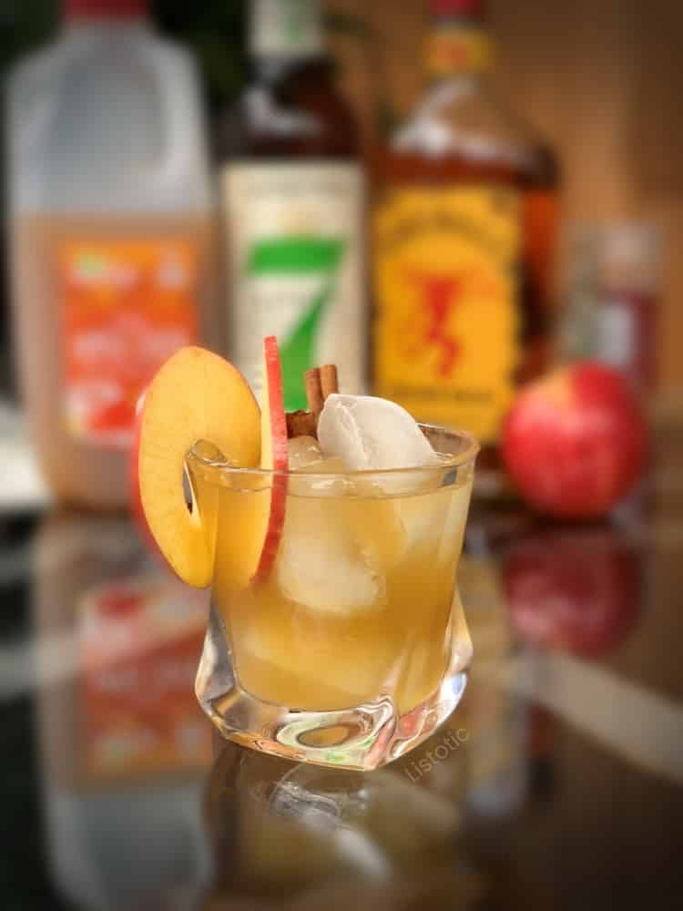 Text Description: Chilled whiskey glass filled with Cinnamon Fireball Whiskey, apple cider, and Seagram's Apple Orchard Whiskey with apple slice garnish and cinnamon stick. Liquor bottles lined up in the background of the cocktail sitting on a glass top table.
