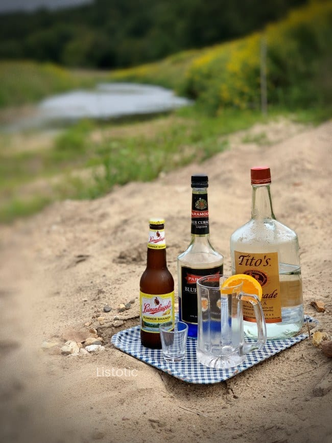 Ingredients for a beer cocktail recipe sitting on a metal tray near a sandy bank of a beautiful country side creek on a summer day.