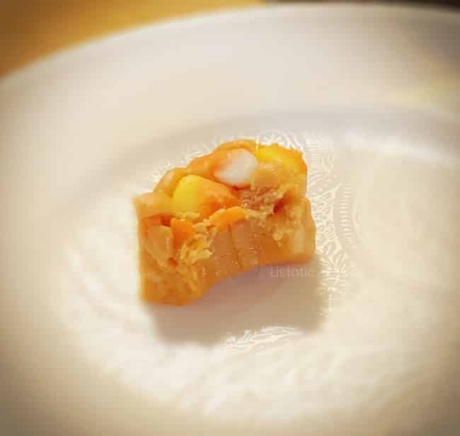 Single piece of candy corn peanut butter fudge with a bite take out of it sitting on a white plate.