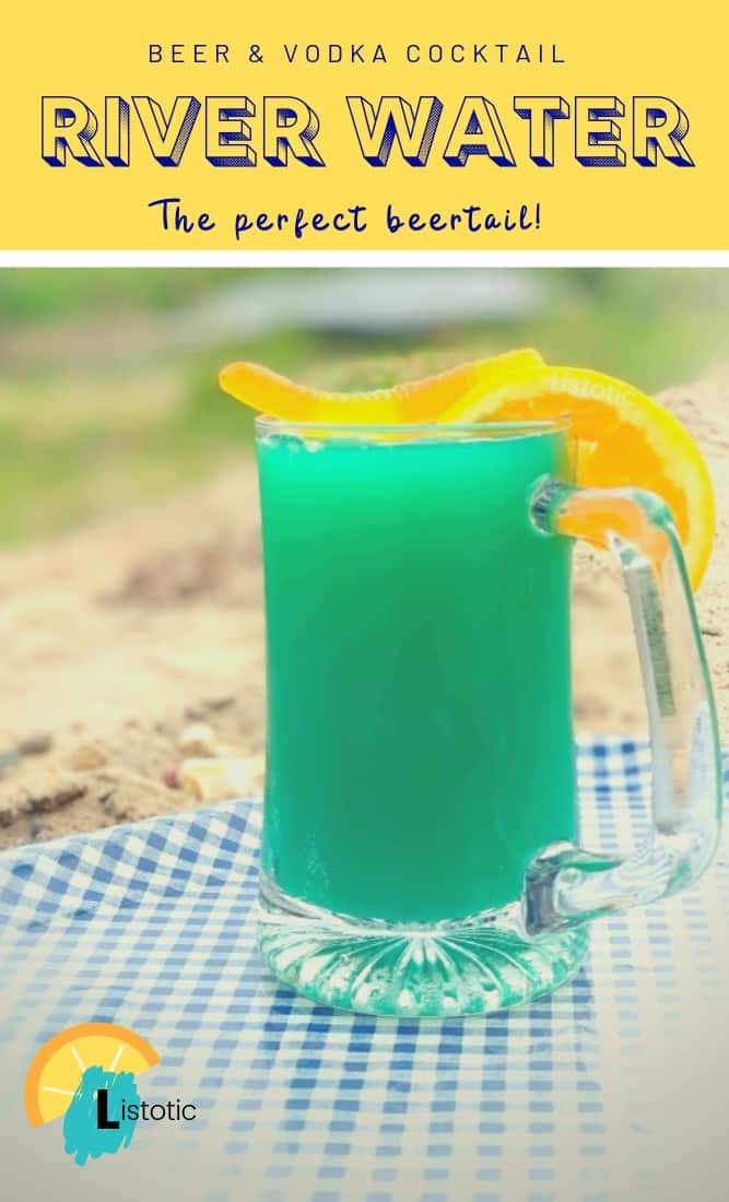 Pinterest image of a blue green colored cocktail with a gummy worm and orange slice garnished on a beer mug on a blue and white gingham metal tray on a sandy river bank on a summer day.