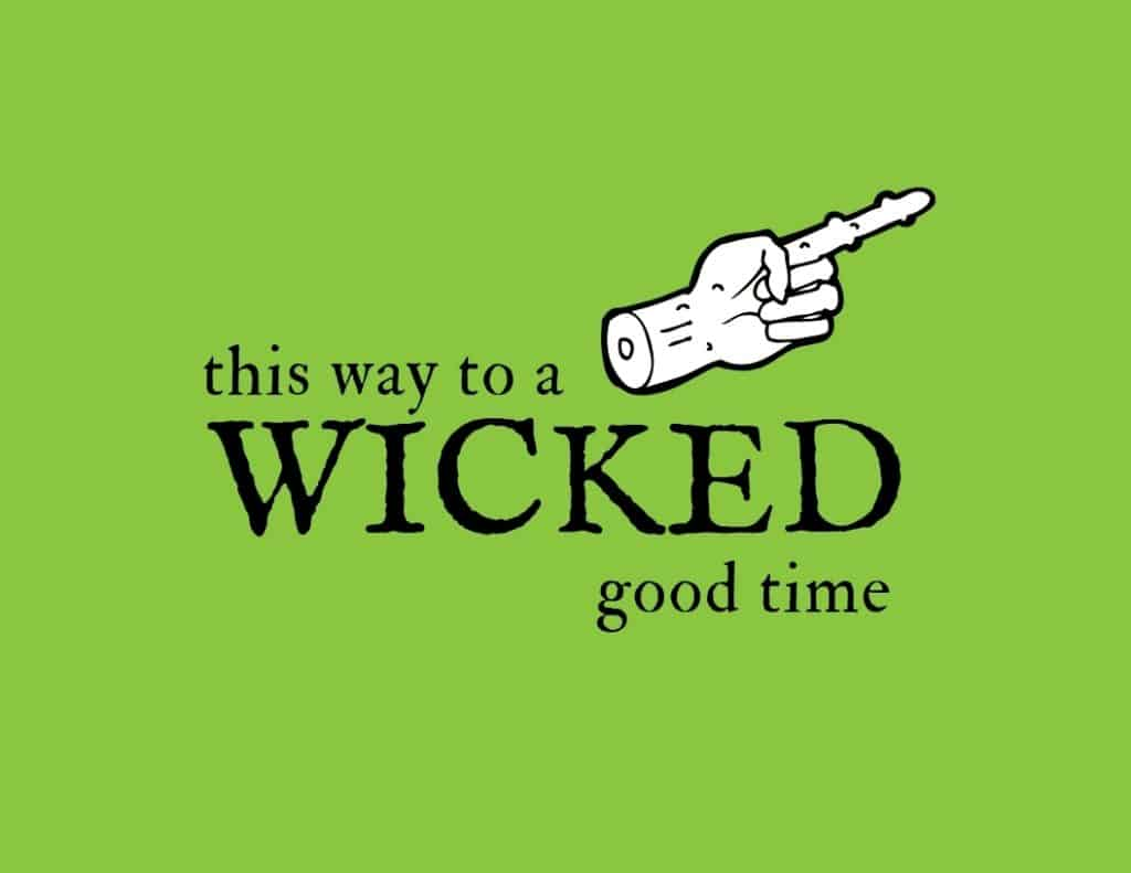 Green sign with a zombie and pointing out that says this way to a wicked good time.