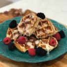 A blue plate with stacked cinnamon roll waffles drizzled in melted cream cheese frosting topped with fresh berries.
