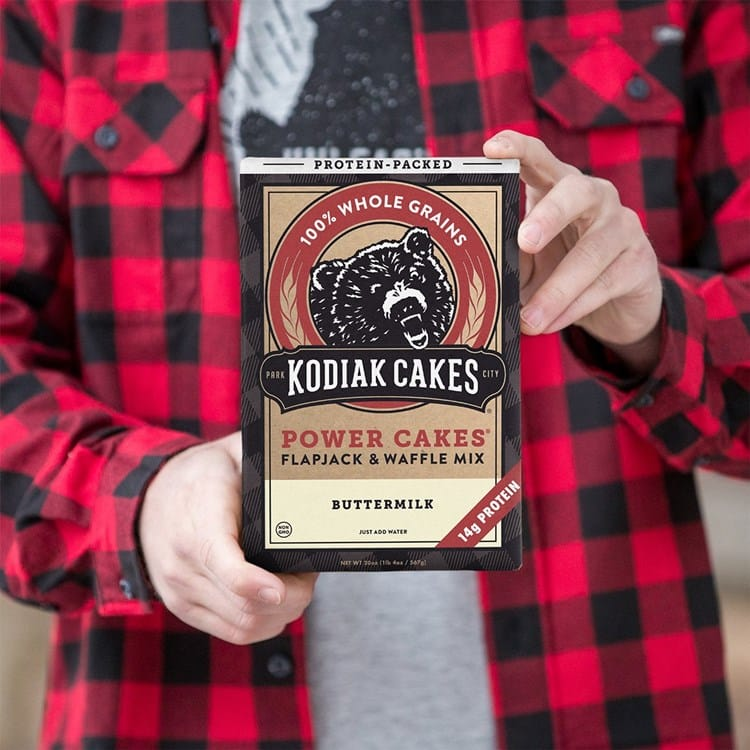Man wearing red buffalo plaid button up holding a box of Kodiak flapjack and waffle mix.