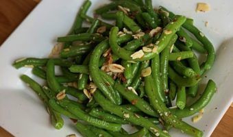 White plate with fresh green beans and slivered almonds.