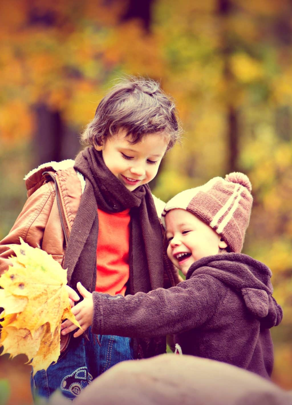Two young boys playing outside on an autumn day with bright yellow and orange fall leaves and smiling.