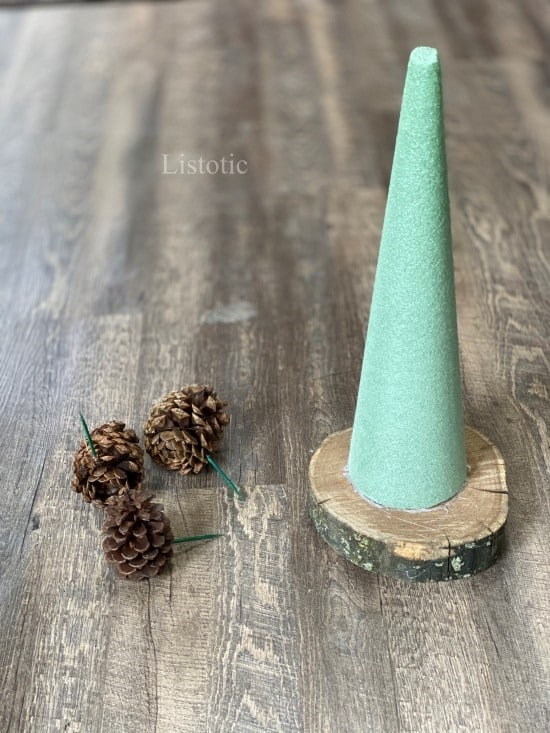 Floral Foam Cone on rustic wood slab and pine cones